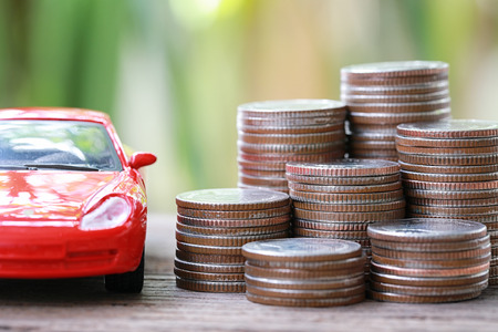 Silver coin of pile with red car model in concept savings to buy a new car or value of car and journey insurance.