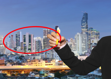 hand of a business women use a pen write red circle to input your text on downtown business district background.