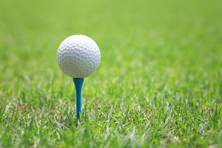 Golf ball on wooden golf tee to embroider on the green lawn prepare for hit.