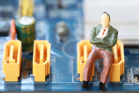 Businessman sit on a computer motherboard in concept of doing business and profiting on technology. Stock Photo