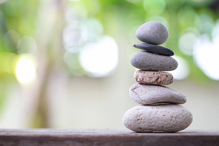 Balance Stones stacked to pyramid in the soft nature green background to Spa ideas design or freedom and stability concept on rocks.