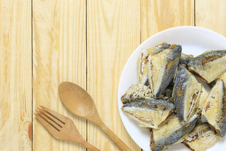grilled fish of thai foods in white dish on wooden floor and have copy space for design in your work.