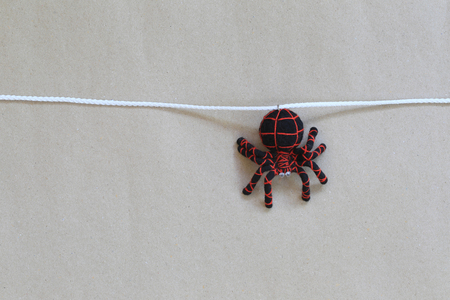 Spider doll hanging on a rope with brown wall background and have copy space for your design in work. Stock Photo