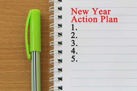Notebooks and new year action plan text  are placed on a brown wooden floor and have copy space for design in your work.