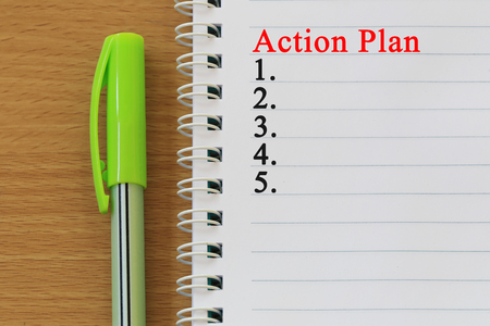 Notebooks and action plan text  are placed on a brown wooden floor and have copy space for design in your work.