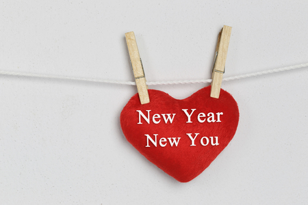 Red heart hanging on a rope and have New year New you text for design Concept in your work.