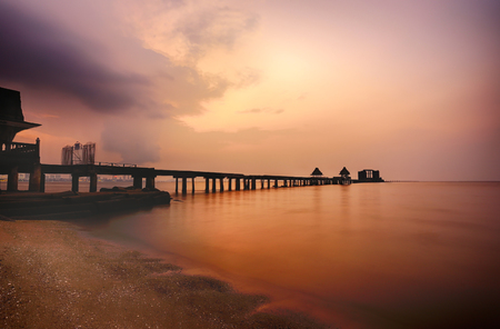 Old bridge in the sea on twilight time after sunset,nature of outdoor tropical coast in Thailand of Popular attractions the name is Wat Jit-ta-pha-wan in Chonburi province.