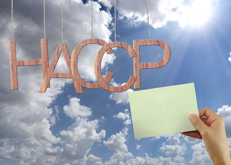 Wooden HACCP text Stands for Hazard Analysis and Critical Control Point hanging on rope and businessman hold a green paper on blue sky background.