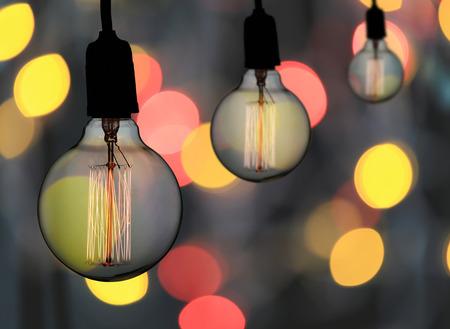 A lâmpada do vintage ou a ampola moderna penduram no teto no fundo do bokeh, no conceito do interior e no projeto em seu trabalho.