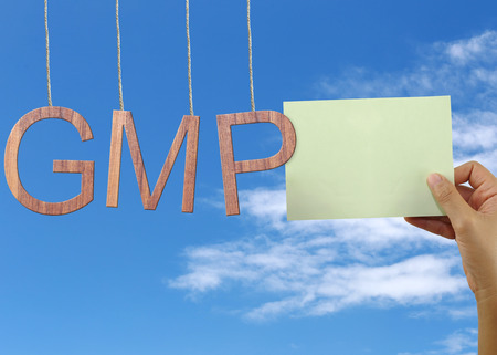 Wooden GMP text Stands for Good Manufacturing Practice hanging on rope and hand of a businessman holding a green note on blue sky background.