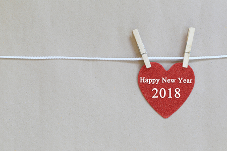 Red heart hanging on a rope and have happy new year 2018 text for design concept of a holiday in your business.