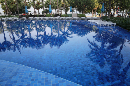 Blue swimming pool of resort in a daytime and reflection of shadow coconut trees on the surface. Editorial