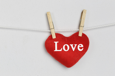 Red heart hanging on a rope and have Love text for design concept of love to present your work. Stock Photo