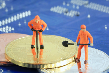 Model people of miners are standing on the gold bitcoin for design in digital concept cryptocurrency or bitcoin currency. Stock Photo