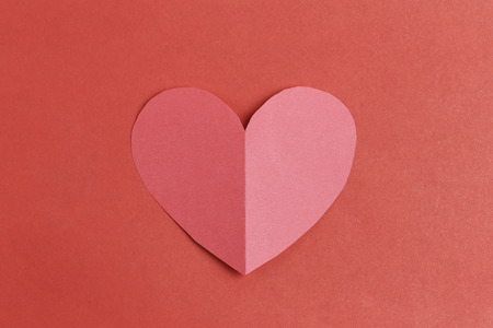 Heart shape of paper on the red cardboard background in Concept for Love and Valentines Day.