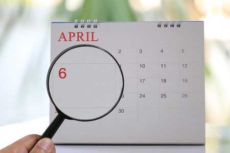 Magnifying glass in hand on calendar you can look Sixth day of month,Focus number one in April,Concept in business and meetings.