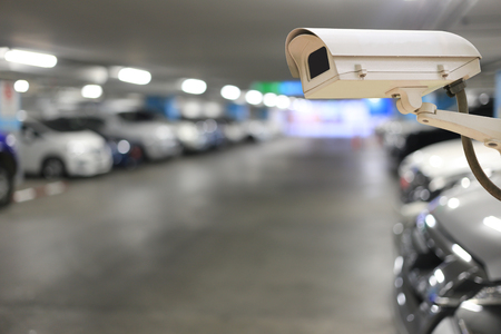 CCTV Camera on blurred cars parking and bokeh light for the Parking location Concept to security and technology.