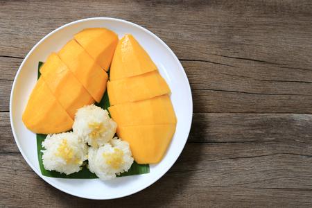 Mango en kleefrijst in witte schotel op houten vloer en hebben kopie ruimte, Dessert was populair in Thailand.