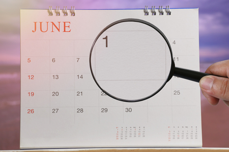 Magnifying glass in hand on calendar you can look first day of month,Focus number one in June,Concept in business and meetings.