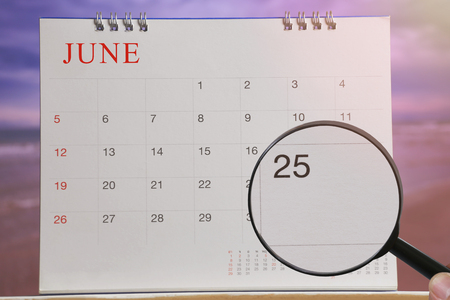 Magnifying glass in hand on calendar you can look Twenty Five day of month,Focus number Twenty Five in June,Concept in business and meetings.