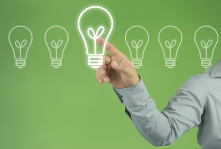 Hand of businessman pointing to a light bulb in the concept of design and ideas on green background. Stock Photo