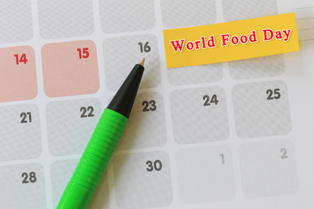 Green pen point to day 16 on calendar paper and have world food day text for the design in you festival concept.