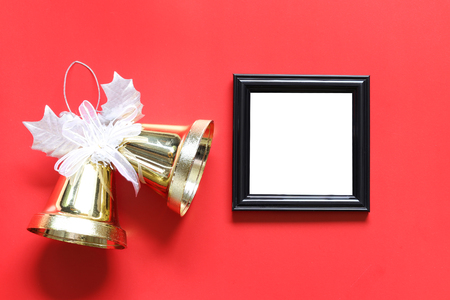 Empty black photo frame and golden bell on red background for design in your work concept.