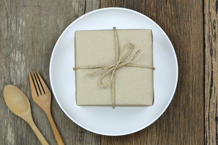 Brown Gift Box in white dish on wooden floor and have wooden spoon for Christmas concept.