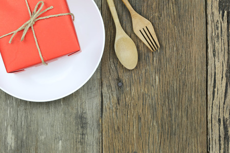 Red Gift Box in white dish on wooden floor and have wooden spoon for Christmas concept. 스톡 콘텐츠