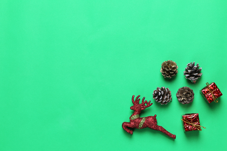 Pine cones and doll deer on a green paper background for design in Christmas concept.