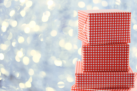 Red Gift Box on Silver Bokeh Backdrop for design in your Christmas concept.