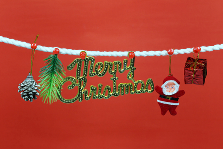 Santa doll hang on the clothesline and have copy space with red background for design in your work concept.
