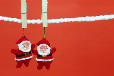 Santa doll hang on the clothesline and have copy space with red background for design in your work concept. Standard-Bild