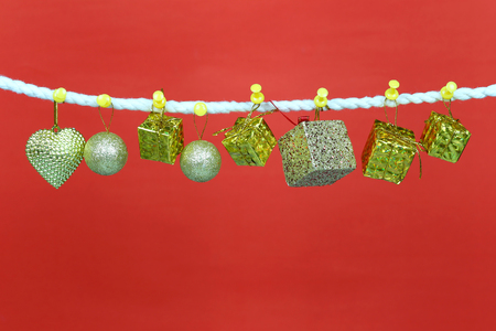 Gold gift box hang on the clothesline and have copy space with red background for design in your work concept. Stock Photo