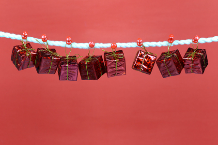 Red gift box hang on the clothesline and have copy space with red background for design in your work concept. Stock Photo