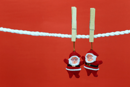 Santa doll hang on the clothesline and have copy space with red background for design in your work concept. Stock Photo