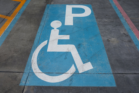 Parking symbol of disabled people on the Concrete road. Фото со стока