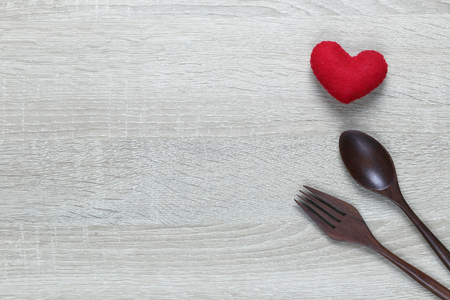 Wooden spoon and dish and red heart on wooden floor with copy space in love or Valentine day concept.