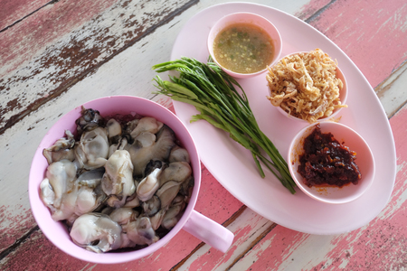 Fresh oysters of Thai seafoods in dish on wooden table.