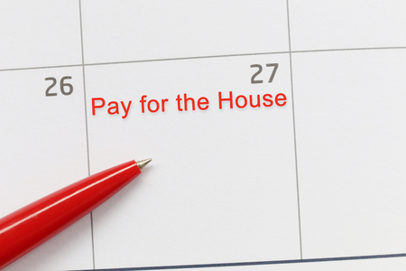 Red pen point to a empty space on the calendar and have Pay of the house text for design in your work concept. Stock Photo