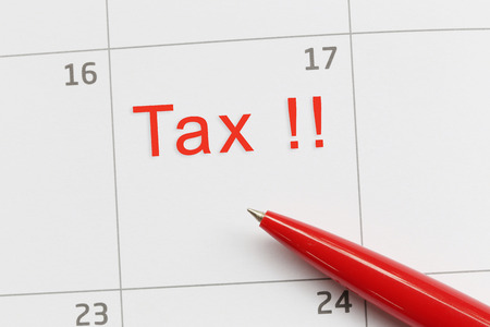 Red pen point to a empty space on the calendar and have Tax day text for design in your work concept. Stock Photo