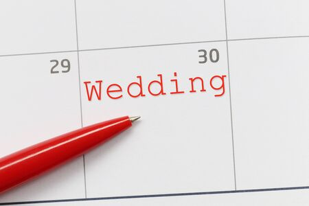 Red pen point to a empty space on the calendar and have Wedding text for design in your work concept. Stock Photo