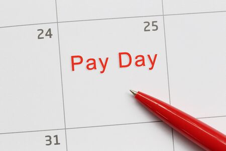 Red pen point to a empty space on the calendar and have Pay day text for design in your work concept.