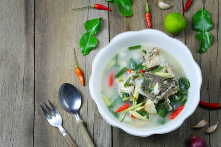 Tom Yum Grouper Fish Spicy Soup of Thai food in a bowl on wooden floor for design in your work foods concept.