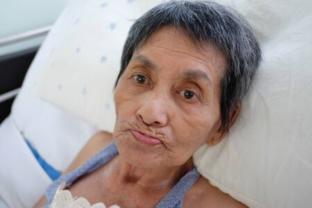 Asian elderly woman lay sick on bed,concept of post-retirement health.
