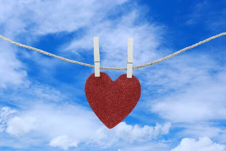 Red heart hanging on a hemp rope on the blue sky background for design in your work concept.