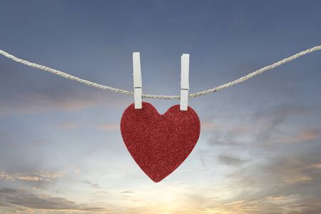Red heart hanging on a hemp rope on the morning sky background for design in your work concept.
