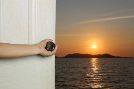 Womans hand is opening the door and have sea and sunset background. Reklamní fotografie