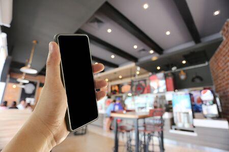 Mano de un hombre que sostiene el dispositivo de teléfono inteligente en el fondo del café café y tiene espacio de copia para el diseño.