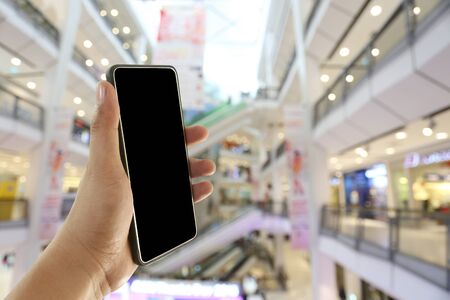 Hand of a man holding smartphone device in the Shopping mall background and have white copy space on screen.